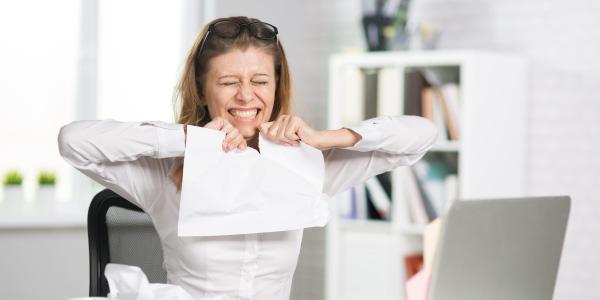 Rascunho da redação dissertativa argumentativa:  mulher rasgando o papel com nervosismo