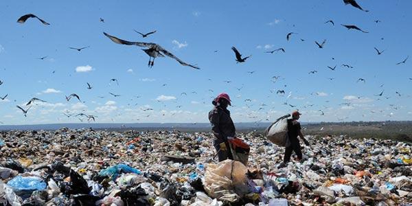 Exercícios sobre Lixo - lixão a céu aberto com dois catadores e muitos urubus