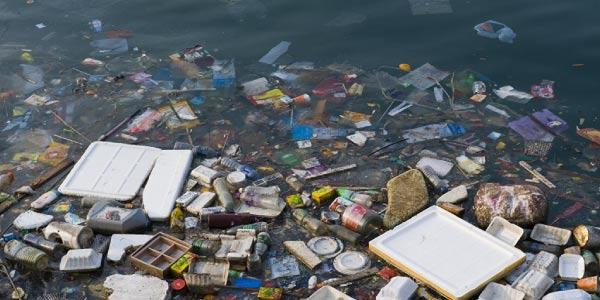 poluiçao da água com diversas embalagens de vidro, plástico, isopor e outros no mar