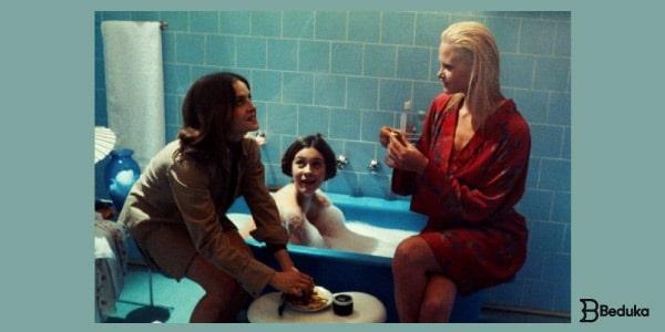 Resumo-de-As-Meninas-três-meninas-sentadas-em-torno-de-uma-banheira-no-banheiro-conversando-animadamente-.-Uma-loira-de-hobby-vermelho-uma-morena-dentro-da-banheira-e-uma-outra-sentada-no-vaso.