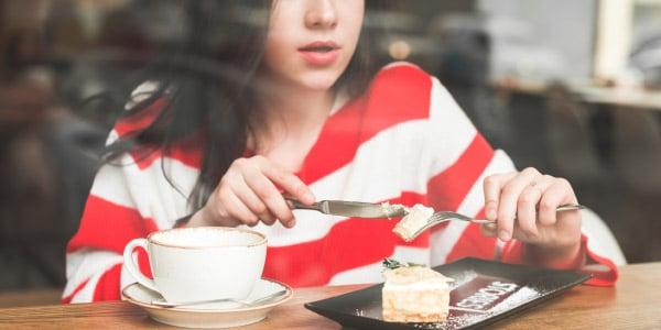 mulher-de-blusa-listrada-comendo-uma-sobremesa-com-café-exemplo-de-ação-contínua-acontecendo-gerúndio