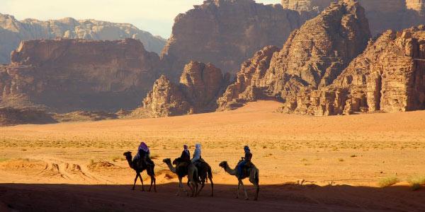 quatro-homens-montados-no-camelo-caminhando-no-meio-do-deserto-com-montanhas-ao-fundo