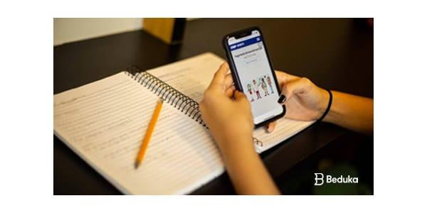 imagem de pessoaestudadno ead por figital com celular na mao e caderno e lapis em baixo
